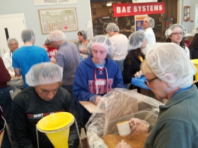 Farook Taufiq and LouAnn Jendro join dozens of volunteers at the Bedford Rotary Club's meal packing event.